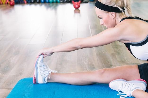 Vrouw doet stretching oefening in de sportschool