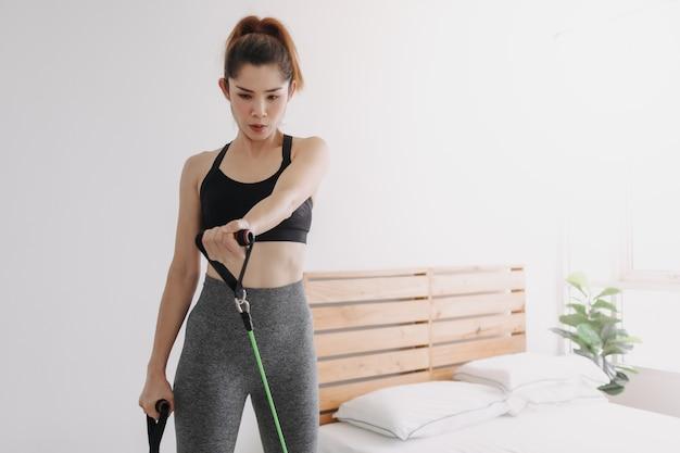 Vrouw doet weerstand slechte cross body bovenborst vliegtraining in haar kamer