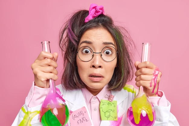 Vrouw doet wetenschappelijk onderzoek gekleed in medische jas houdt glazen bekers met kleurrijke vloeistof verrast door resultaten van experiment draagt bril op roze
