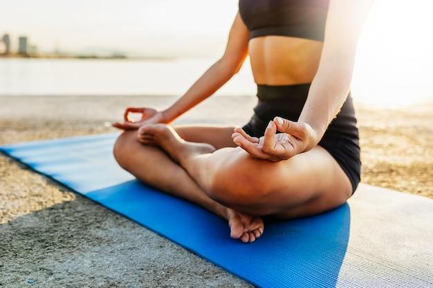 Vrouw doet yoga aan zee bij zonsopgang - sportieve jonge vrouw die mediteert in lotushouding op het strand - wellness en gezondheidszorg lifestyle concept - focus aan de hand