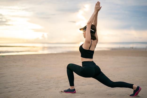 Vrouw doet yoga asana low lunge op het strand met zonsopgang op de ochtend.