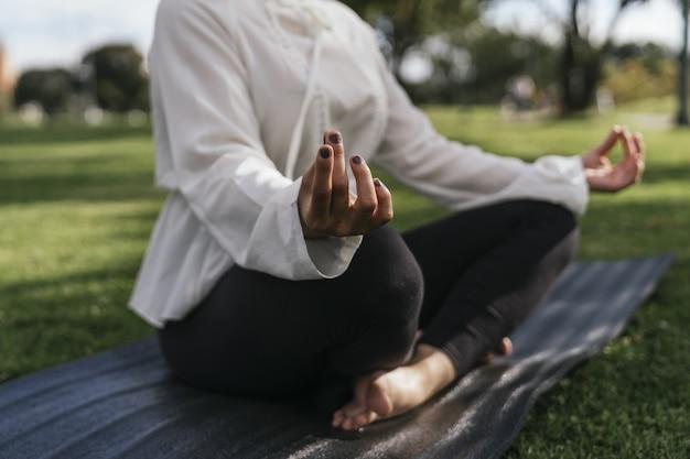 Vrouw doet yoga buiten in een park