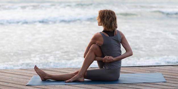 Vrouw doet yoga buiten op de mat