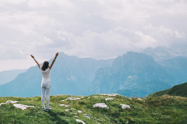 Vrouw doet yoga en mediteert in lotuspositie op de achtergrond van lucht en bergen