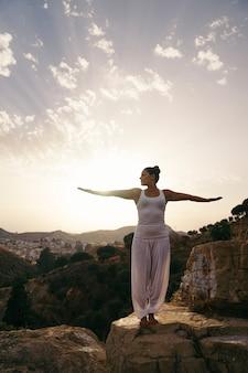 Vrouw doet yoga en rek armen