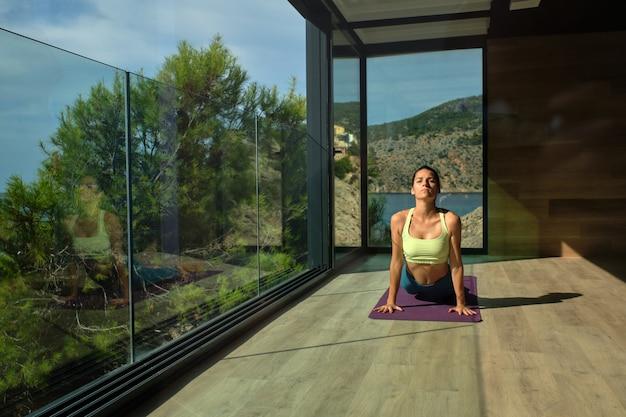 Vrouw doet yoga in cobra pose met gesloten ogen