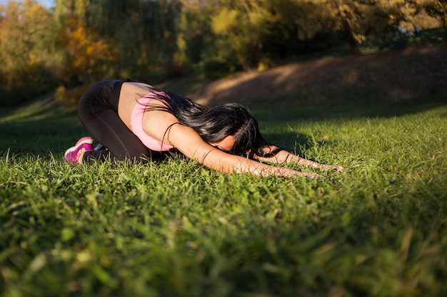 Vrouw doet yoga in de natuur in het park. balasana of de positie van een kind. tijdens zonsondergang