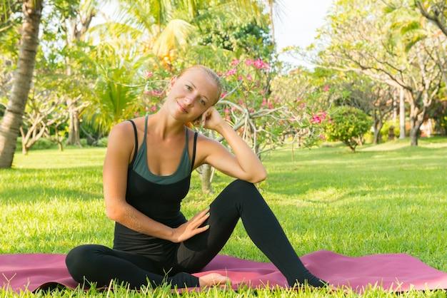 Vrouw doet yoga in de tuin