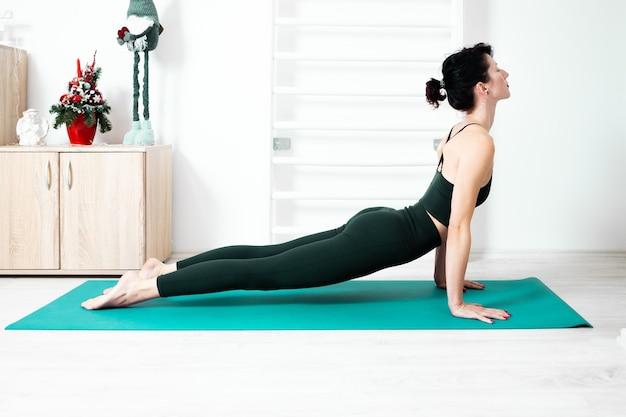 Vrouw doet yoga in haar huis