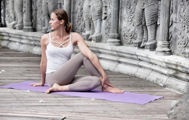Vrouw doet yoga in verlaten tempel. outdoore