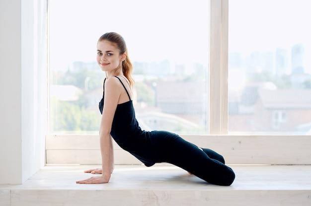 Vrouw doet yoga oefening workout flexibiliteit bij het raam