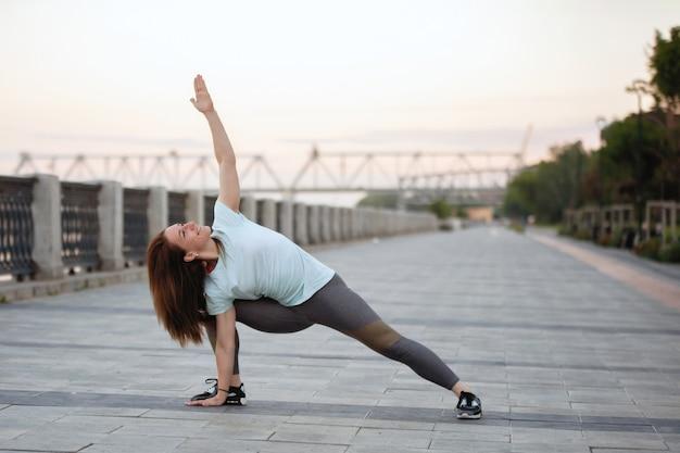 Vrouw doet yoga-oefeningen in opleiding op een dijk in de zomer.