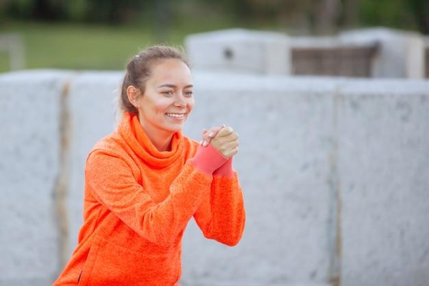 Vrouw doet yoga-oefeningen in opleiding op een stadsstraat in de zomer. middelste plan.