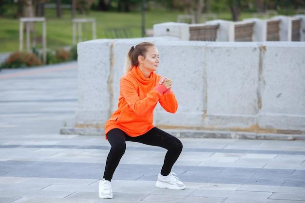 Vrouw doet yoga-oefeningen in opleiding op een stadsstraat in de zomer.