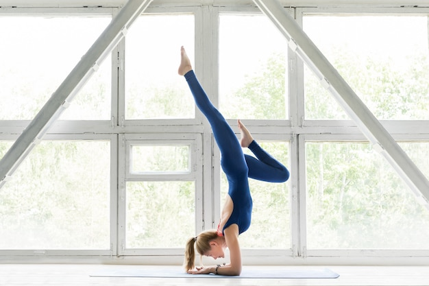 Vrouw doet yoga of pilates oefening en handstand pose.
