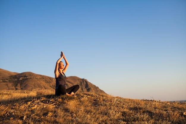 Vrouw doet yoga op de natuur buiten bij zonsopgang