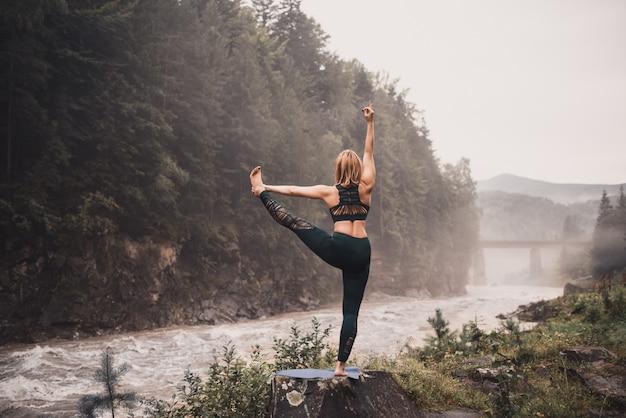 Vrouw doet yoga op een rivieroever