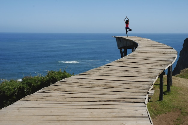 Vrouw doet yoga op het dok met het prachtige uitzicht op de oceaan