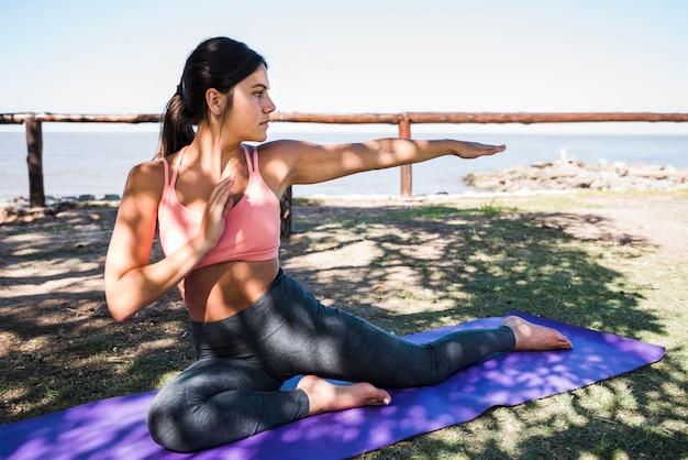 Vrouw doet yoga op het strand