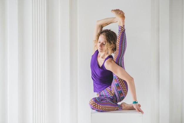 Vrouw doet yoga op kubus