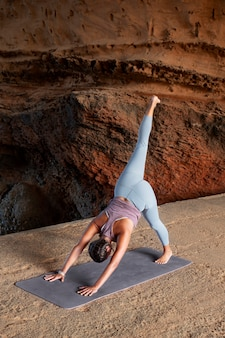 Vrouw doet yoga pose op mat full shot