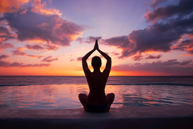Vrouw doet yoga tegen de ondergaande zon.