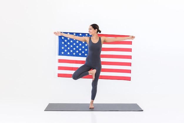 Vrouw doet yoga terwijl ze op tapijt staat met amerikaanse vlag