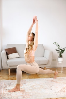 Vrouw doet yoga thuis in de woonkamer living