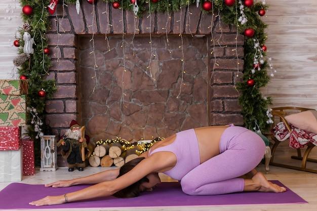 Vrouw doet yoga thuis, nieuwjaar kerstmis achtergrond.