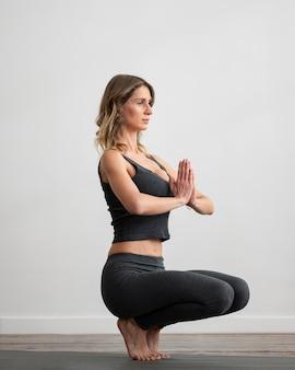 Vrouw doet yoga thuis