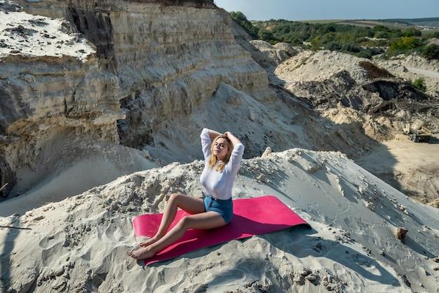 Vrouw doet yoga uitrekkende oefeningen op de mat bij de steengroeve van het natuurzand. meditatie