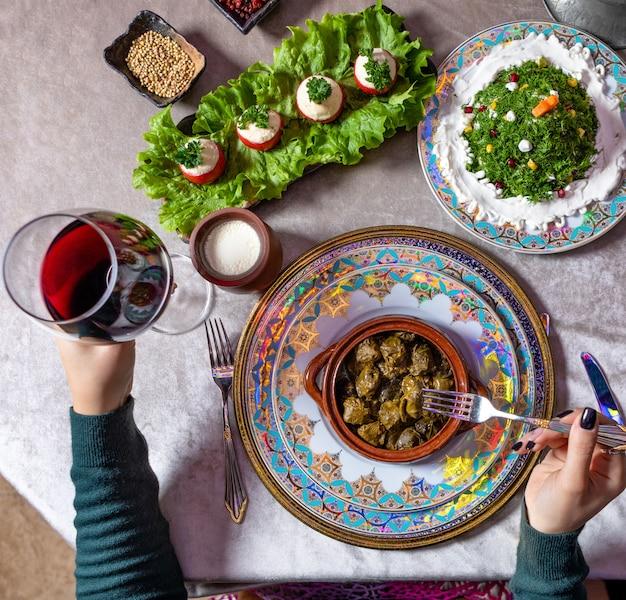 Vrouw dolma eten, met rode wijn bovenaanzicht