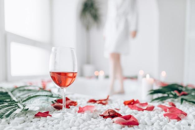 Vrouw dompelt benen in het bad, decor van rozenblaadjes