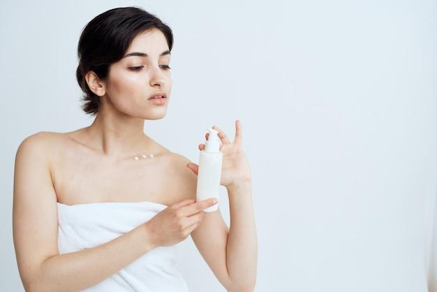 Vrouw doodde handdoeken met lotion op blote schouders