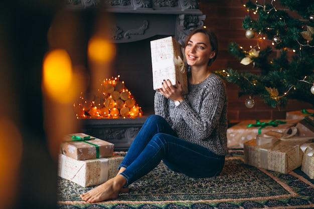 Vrouw door kerstboom presenteert uitpakken