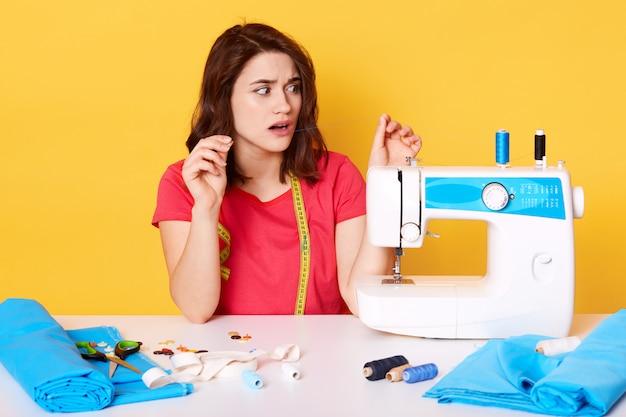 Vrouw draad aanbrengend naaimachine