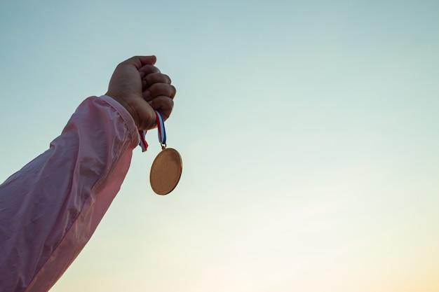 Vrouw draag roze shirts met lange mouwen houdt gouden medaille