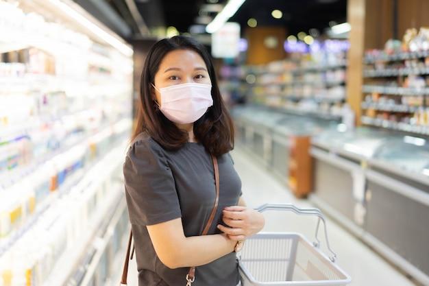 Vrouw draagt beschermend gezichtsmasker in supermarkt voor nieuw normaal levensstijlconcept
