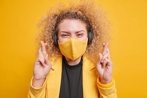 Vrouw draagt beschermend gezichtsmasker tegen coronavirus wenst succes houdt vingers gekruist luistert muziek via koptelefoon gekleed in elegante kleding