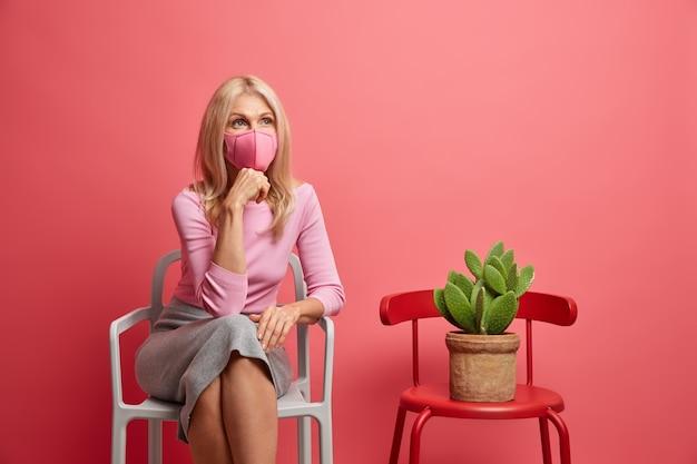 Vrouw draagt beschermend masker blijft thuis tijdens quarantaine voorkomt coronavirus gekleed in casual trui en skir zit alleen op stoel