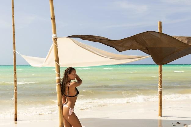 Vrouw draagt bikini is poseren op het strand