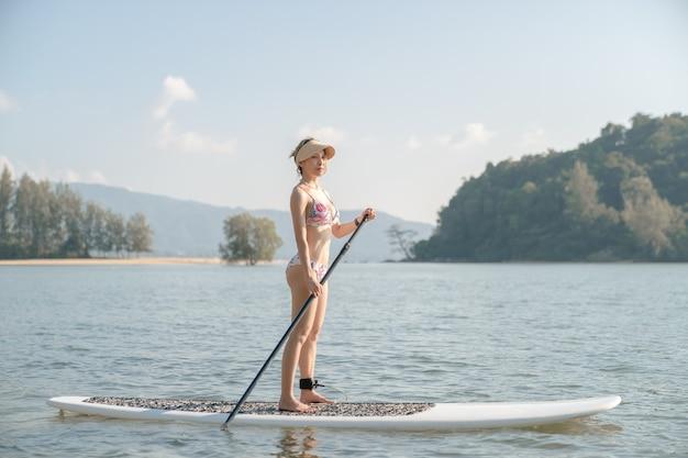 Vrouw draagt ?? bikini op stand-up paddle board of sup in de zee. watersport