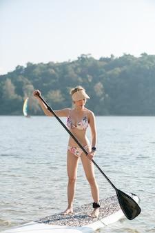 Vrouw draagt bikini op stand-up paddle board of sup in de zee. watersporten, actieve levensstijl.