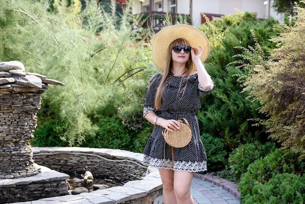 Vrouw draagt blauwe jurk in zomertuin, lifestyle