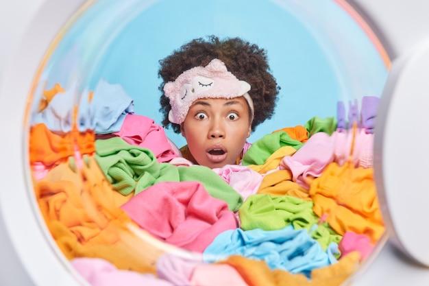 Vrouw draagt blinddoek voelt verbijsterd stokken hoofd door grote stapel wasgoed poses vanuit binnenkant wasmachine