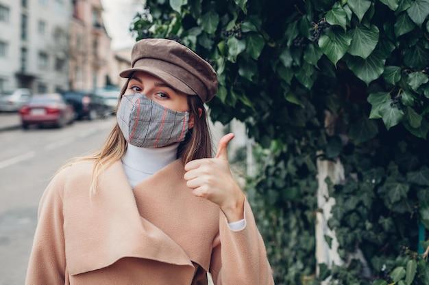 Vrouw draagt buitenshuis herbruikbaar masker tijdens coronavirus covid-19 pandemie. vrouw verschijnt duim op lege straat. blijf veilig