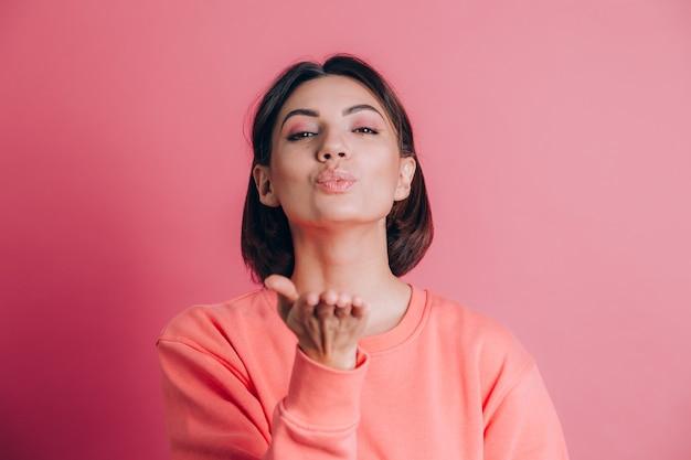 Vrouw draagt casual trui op achtergrond glimlachend kijken naar de camera blaast een kus met de hand op lucht wordt mooi