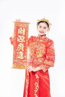 Vrouw draagt cheongsam-pak blij met het krijgen van de chinese wenskaart van de baas in chinees nieuwjaar