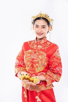 Vrouw draagt cheongsam-pak en geeft goud aan haar familie voor geluk in chinees nieuwjaar