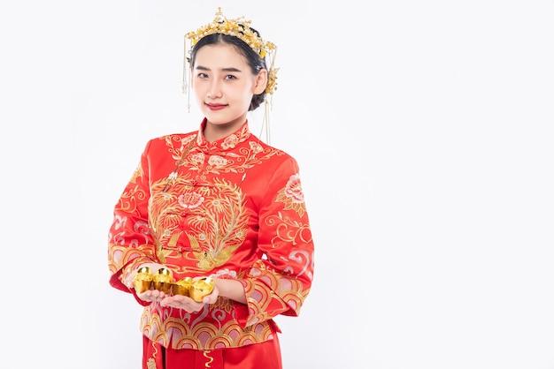 Vrouw draagt cheongsam-pak en kroon geeft goud aan haar familie voor geluk in chinees nieuwjaar